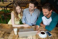 Vue courbe des amis regardant l'ordinateur portable numérique Photos libres de droits