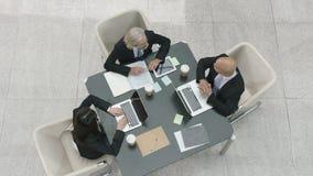 Vue courbe des cadres d'entreprise arrivant lors de la réunion d'affaires banque de vidéos