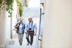 Vue courbe des couples d'une cinquantaine d'années tenant des mains tout en s'élevant fait un pas dehors photographie stock libre de droits