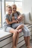 Vue courbe des enfants de mêmes parents caucasiens heureux doux fille et garçon d'enfants jouant l'étiquette à la maison Photos stock