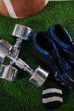 Vue courbe des haltères par des sports chaussure et football américain Image libre de droits