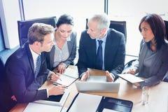 Vue courbe des hommes d'affaires agissant l'un sur l'autre dans la salle de conférence Photo stock