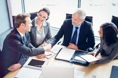 Vue courbe des hommes d'affaires se serrant la main dans la salle de conférence Photographie stock