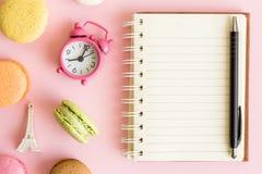Vue courbe des macarons multicolores, du réveil, du petit Tour Eiffel et du bloc-notes vide sur le fond rose Image libre de droits