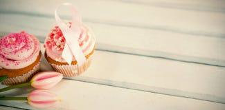 Vue courbe des rubans de rose de conscience de cancer du sein sur des petits gâteaux avec des tulipes photographie stock