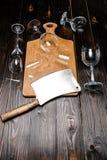 Vue courbe des verres à vin et de la hache cassés avec le conseil en bois Photographie stock