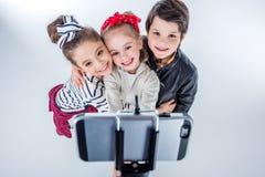 Vue courbe du garçon et des filles de sourire faisant le selfie Photo libre de droits