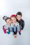 Vue courbe du garçon et des filles de sourire faisant le selfie Images libres de droits