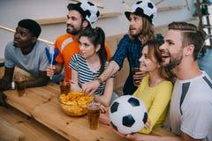 vue courbe du groupe multiculturel de sourire d'amis dans des chapeaux de ballon de football buvant de la bière et observant le m image stock