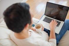 Vue courbe du jeune homme à l'aide de son ordinateur portable Photo libre de droits