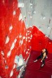 Vue courbe du mur de pratique de femme s'élevant sur un panneau de campus Femme s'élevant sur un panneau de campus à s'élever de  photographie stock