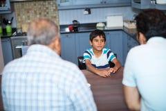 Vue courbe du père et du grand-père parlant au garçon Images stock