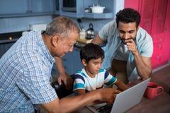 Vue courbe du père et du grand-père regardant le garçon Photos libres de droits