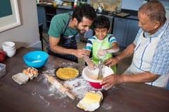 Vue courbe du père et du grand-père regardant le garçon faisant la nourriture Photo stock