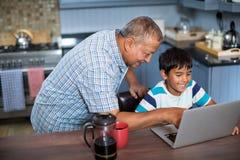 Vue courbe du petit-fils de assistance première génération à l'aide de l'ordinateur portable Images libres de droits