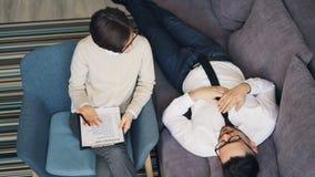 Vue courbe du thérapeute et du patient parlant dans le bureau pendant la consultation banque de vidéos