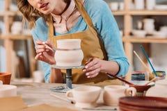 vue cultivée de femme peignant la cruche en céramique image stock