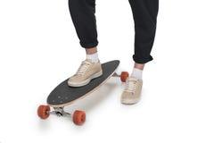 Vue cultivée de jeune homme dans les jeans noirs et des espadrilles se tenant sur le longboard Photos stock