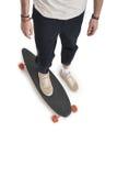 Vue cultivée de jeune homme dans les jeans noirs et des espadrilles se tenant sur le longboard Photographie stock