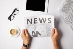vue cultivée de journal de lecture d'homme d'affaires à la table blanche avec le comprimé numérique, le café et les lunettes images stock