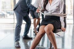 Vue cultivée de limite de femme d'affaires avec la corde sur la chaise et d'hommes d'affaires la tirant Image stock
