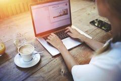 Vue cultivée de tir de la jeune étudiante futée apprenant en ligne par l'intermédiaire de l'ordinateur portable avant ses confére Photographie stock libre de droits