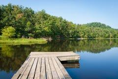 Vue d'été d'un petit lac de pays avec le pilier en bois. Photographie stock