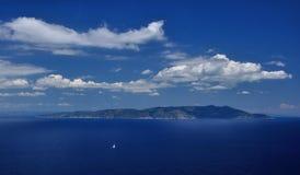 Vue d'île avec les nuages de bateau et le ciel, Giglio, Toscane, Italie Image libre de droits