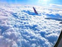 Vue d'aile d'un vol d'avion au-dessus des nuages Nuages et ciel par une fenêtre d'avion Photo stock