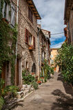 Vue d'allée avec les maisons et les usines en pierre dans le soleil de matin dans Vence Photo libre de droits
