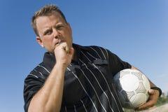 Vue d'angle faible d'arbitre du football montrant la carte jaune contre le ciel bleu Photographie stock