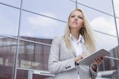 Vue d'angle faible de femme d'affaires tenant le comprimé numérique tout en regardant loin contre l'immeuble de bureaux Photographie stock