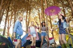 Vue d'angle faible de jeunes amis heureux dansant au terrain de camping Photos stock