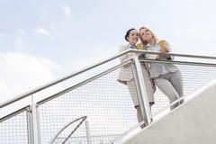 Vue d'angle faible de jeunes femmes d'affaires avec les tasses de café jetables se tenant prêt la balustrade contre le ciel Photographie stock