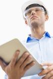 Vue d'angle faible de l'architecte masculin tenant la tablette contre le ciel image libre de droits