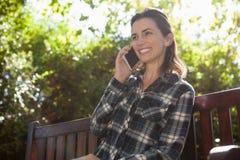 Vue d'angle faible de la belle femme de sourire parlant au téléphone portable tout en se reposant sur le banc en bois Photo libre de droits
