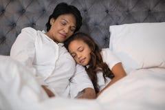 Vue d'angle faible de la grand-mère et de la petite-fille faisant une sieste sur le lit Photographie stock libre de droits