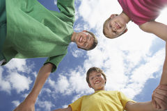 Vue d'angle faible de trois enfants tenant des mains Images stock