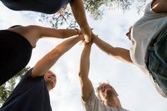 Vue d'angle faible des amis empilant des mains contre le ciel Images libres de droits