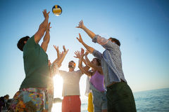 Vue d'angle faible des amis jouant le volleyball sur le rivage Images libres de droits