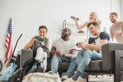 vue d'angle faible des amis multi-ethniques heureux avec le jeu de manettes images stock