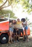 Vue d'angle faible des amis regardant la carte le terrain de camping Photo libre de droits