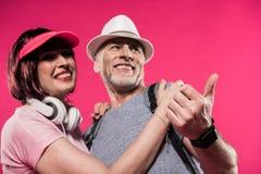 Vue d'angle faible des couples de sourire dans l'habillement élégant regardant loin Image libre de droits