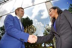 Vue d'angle faible des couples ethniques multi d'affaires se serrant la main Photos stock