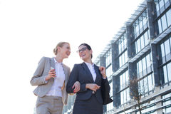Vue d'angle faible des femmes d'affaires heureuses marchant en dehors de l'immeuble de bureaux contre le ciel clair Images stock