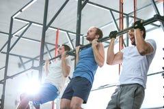 Vue d'angle faible des hommes consacrés faisant menton-UPS dans le gymnase de crossfit Image libre de droits