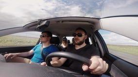 Vue d'appareil-photo de gopro du groupe des jeunes voyageant en voiture ensemble Amis montant par la route de campagne banque de vidéos