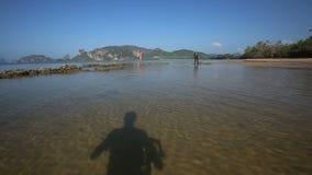 Vue d'appareil-photo mobile le long de l'eau vers des modèles sous la marée basse banque de vidéos