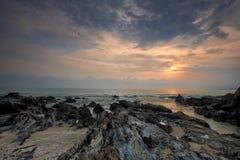 Vue d'aube de plage de sable avec des roches Photos stock