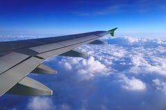 Vue d'avion de la fenêtre des cumulus ci-dessous et du ciel bleu image stock